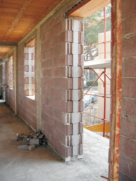 Hollow concrete block / for load-bearing walls / with integrated ...