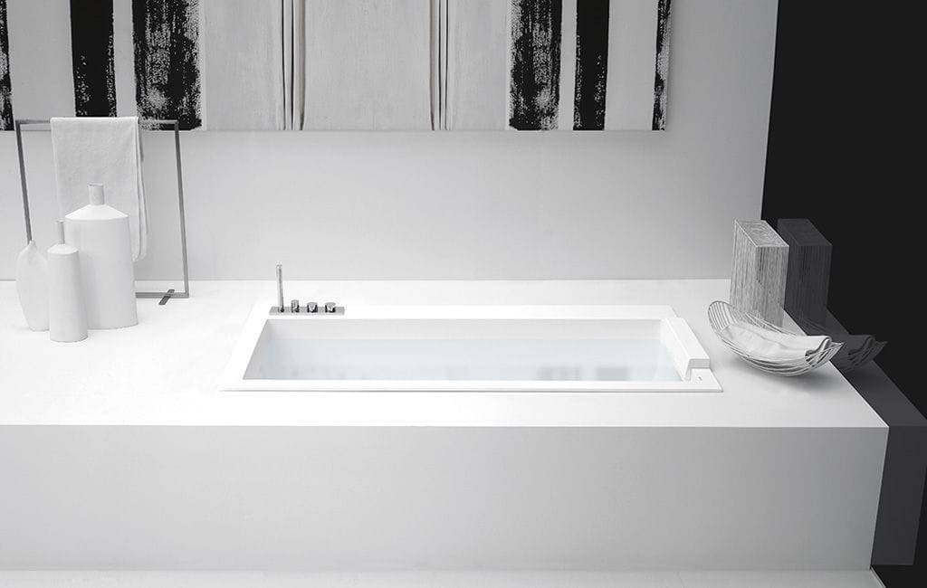 Free-standing bathtub / built-in / Corian® / with integrated ...