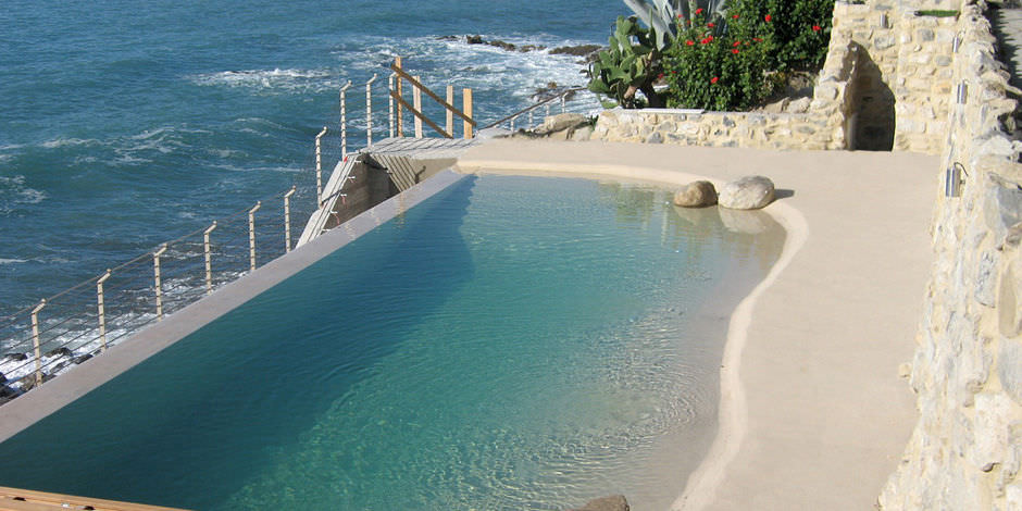 In-ground swimming pool / stone / natural / overflow - Biodesign Pools