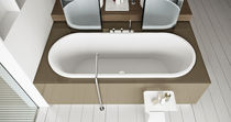Oval bathtub / Corian® / resin / marble