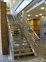 straight staircase with a lateral stringer for commercial buildings (metal frame and steps)  Couturier Iron Craft