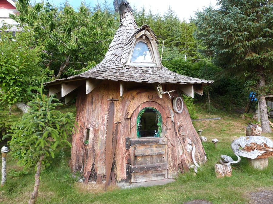 tiny hobbit home carved from a stump is straight out of a fairytale