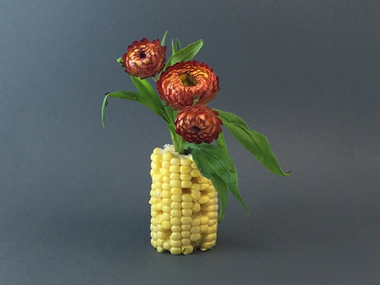 fall flowers are contained in a yellow ear of corn vase