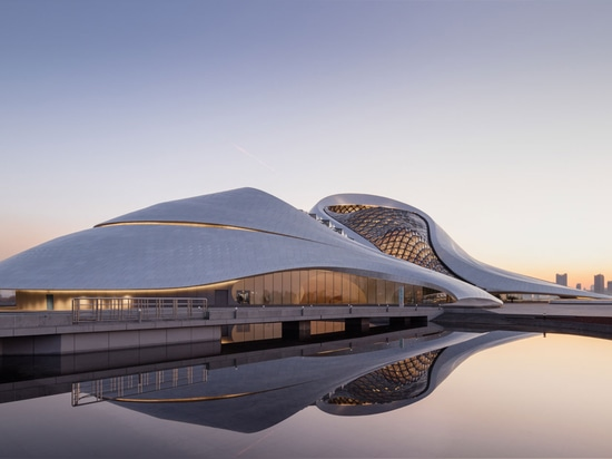 Sitting in the country's fairly remote and cold north-east provinces, the curvaceous opera house is set within the wetlands of the Harbin Cultural Island. Photography: Adam Mork