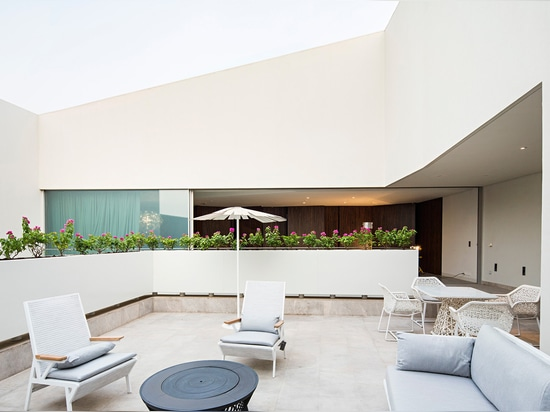 A large open-air terrace, accessible from one of the home's sleeping quarters, is placed on the top floor of the property