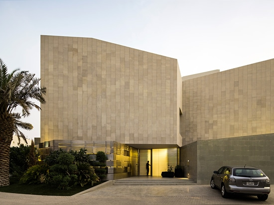 The house's distinct stone skin encases the whole volume. Only when entering the home are its several interior courtyards and large internal windows revealed.