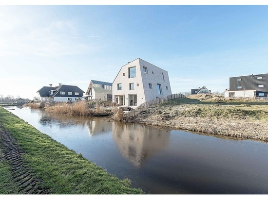 global architects' asymmetric rock house emerges from dune landscape in holland