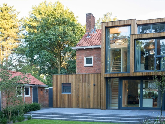 Timber-clad extension reconnects post-war Dutch residence with nature