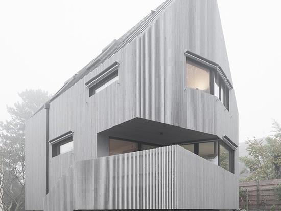 karawitz wraps asymmetric home entirely in grey larch wood in france