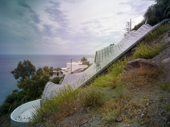 the house is buried into the steep slope and benefits from the annually constant temperature of 19.5 degrees celsius