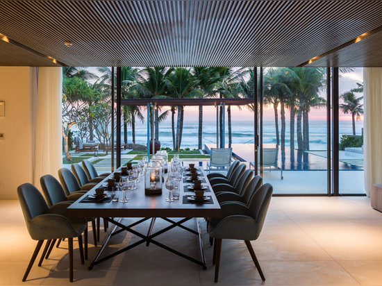 a large dining table looks out towards the ocean