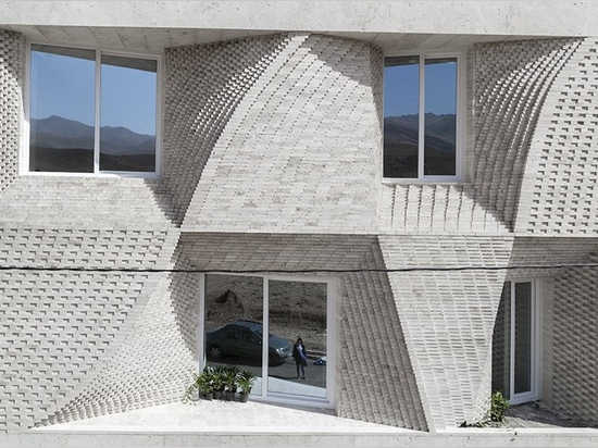 travertine building in mahallat, iran, is decorated by brick patterns, by caat studio