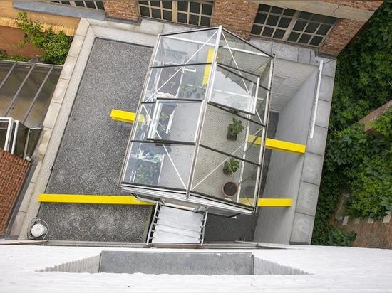 dmvA suspends greenhouse for urban farming over steel rods in belgium