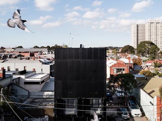 DKO + SLAB add black metal screen façade to vertical dwellings in australia