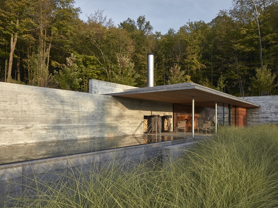 This Pool House Features Long Board-Formed Concrete Walls And An Outdoor Fireplace