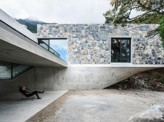 Stone boxes rise into a forest canopy on a sculpted concrete base
