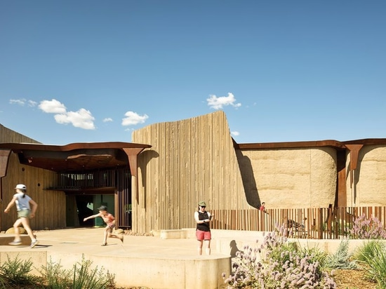 In colour, texture and form, the building appears as a geological monolith that belongs to the outback landscape.