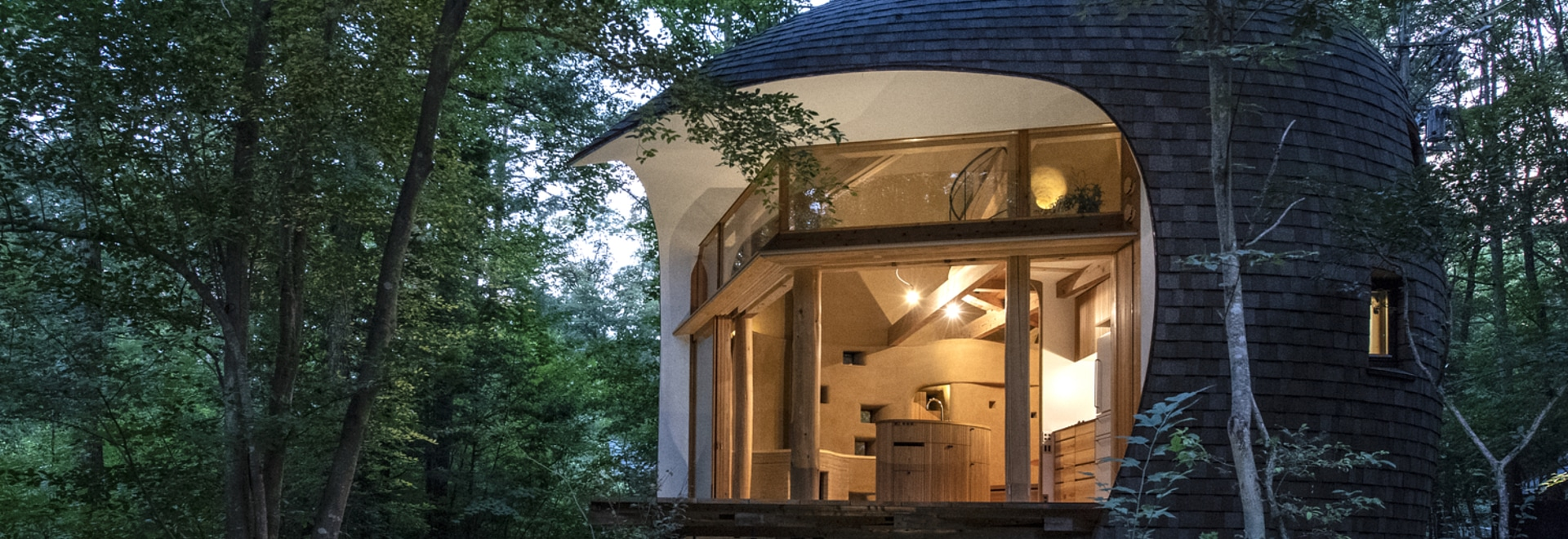 A Small House Shaped Like A Shell Is Surrounded By A Japanese Forest