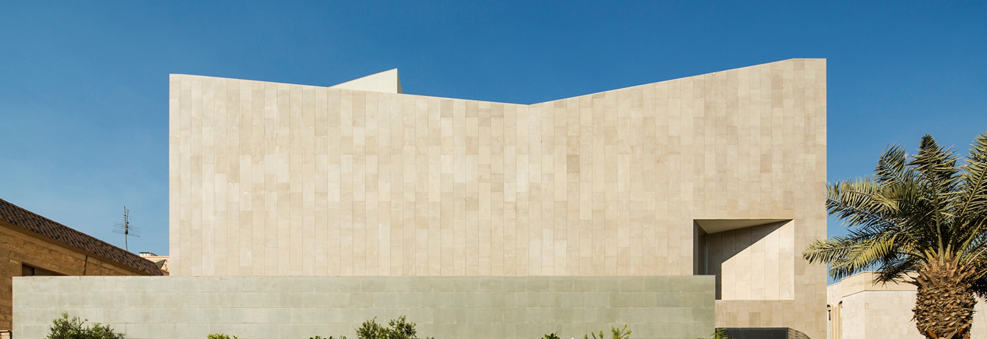 The Wall House by AGi architects is a new, stone-clad family home, located in the suburbs of Kuwait City