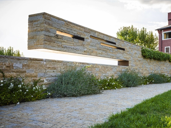 the wall culminates in a barbecue space within the private garden