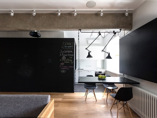 The dining room also boasts a few neat features. The table hangs from a chain on the ceiling, the other side resting on a structural pipe. When the family needs more floor space for entertaining, i...