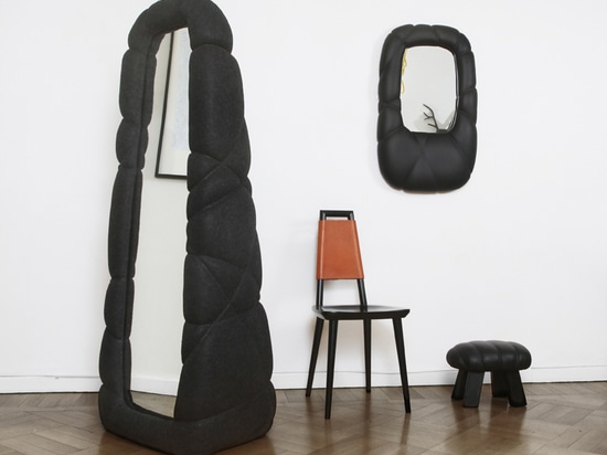 the textile and leather body gives the mirror more presence within the interior
