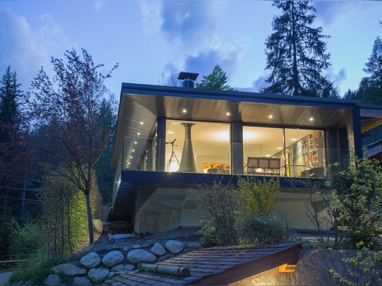 surrounded by natural rock faces, the chalet appears as a fortress, nestled into the rugged terrain
