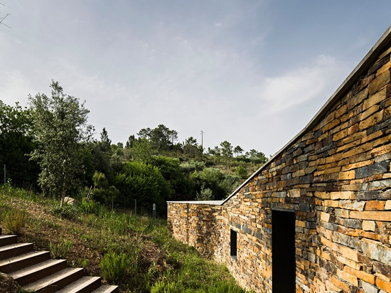 the home is accessed through a wall that evokes the region's traditional slate buildings