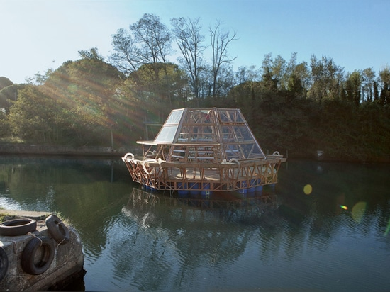 a wooden base floats on recycled plastic drums and supports a glass greenhouse