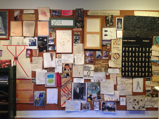 Mementos are pinned to a board in the designer's studio