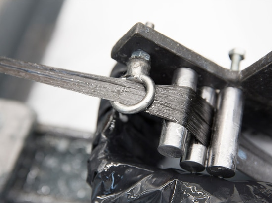 Lengths of carbon and glass fibre are drawn through a resin bath by the robot, and then wound around metal scaffolding