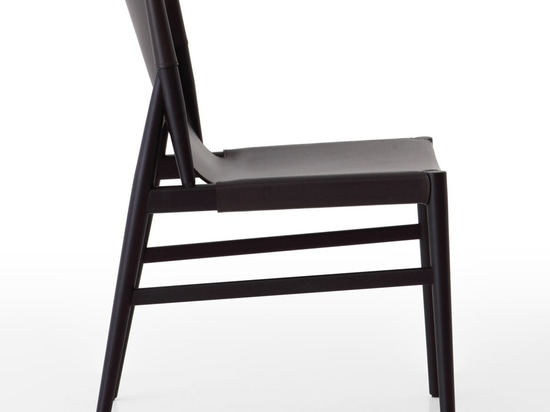 The Voyage chair features tapered wooden legs, in either natural or black stained maple