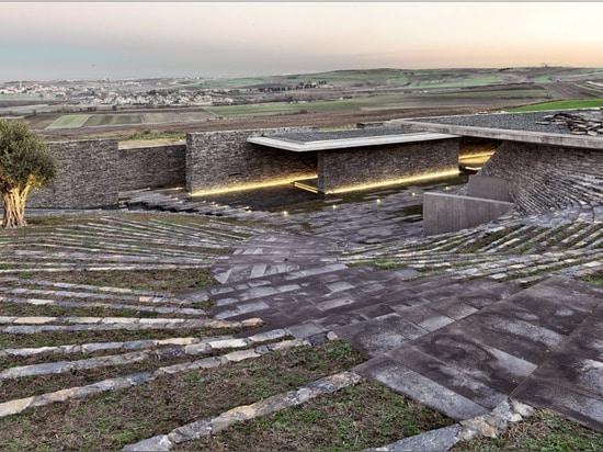 Terraced landscaping surrounds concrete and stone structure of Emre Arolat's Sancaklar Mosque