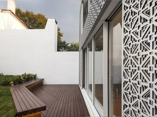 Lace-like screen inspired by Portuguese tiles cover the rear facade of the charming Restelo House in Lisbon