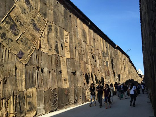 """Arsenale buildings covered in sacks used in the unregulated export of cocoa from Ghana: Ibrahim Mahama's """"Out of Bounds""""."""