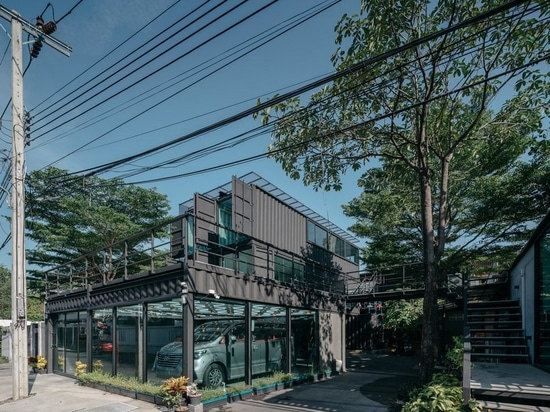 archimontage stacks shipping containers to form 'carcare' center in bangkok