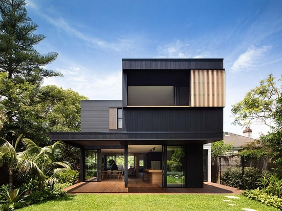 The Exterior Of This House Has Blackened Wood Siding With Contrasting Light Wood Shutters