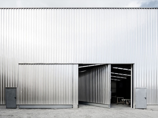 Corrugated steel warehouse encloses colourful office buildings in Portugal
