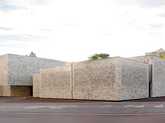 The new brick facade wraps around the preexisting concrete structure built in the 1970s. (Luc Boegly)
