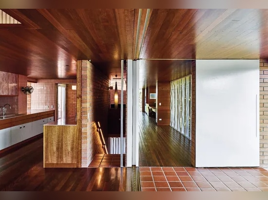 The kitchen incorporates spotted gum and brush box joinery and mid-century pink tiles.