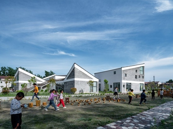 kindergarten in rural china organized as a 'mini village' of scattered volumes