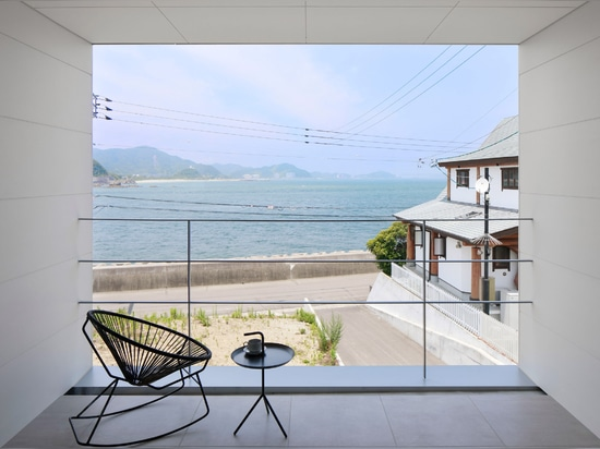Slim white house by CAPD frames view of the sea in Japan