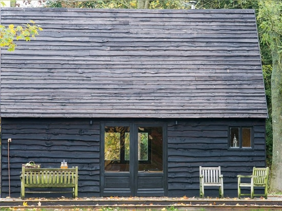 woodland cabin by de rosee sa is finished with upcycled tractor engine oil