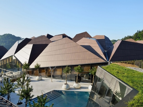 Enota encloses pool in Slovenia with geometric roof