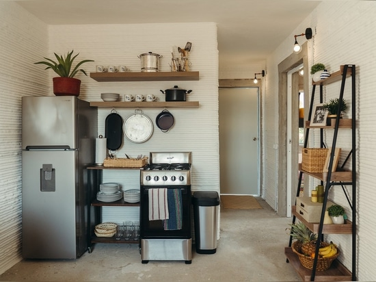 A modest kitchen offers the essentials: an oven with a range, a refrigerator, and shelving.