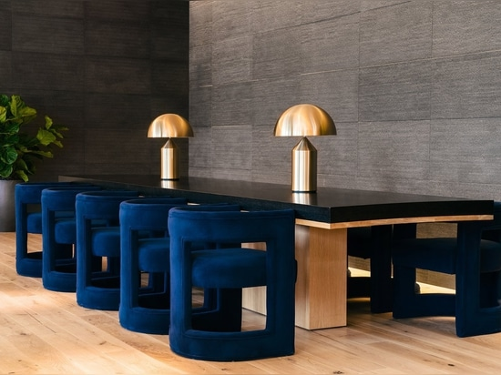 Deep blue velvet chairs, brass lamps, and polished concrete add decadence that's characteristic of both Industrious and Equinox.