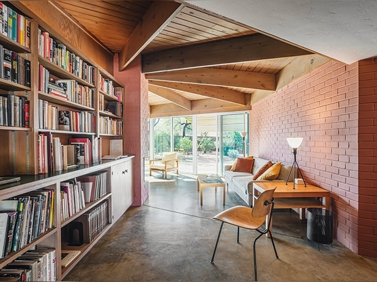 High wood beams meet floor-to-ceiling bookshelves in the entryway. The brick continues throughout the interior.