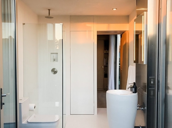 The compact bathroom is outfitted in Designer White Corian surfaces and high-end fixtures.