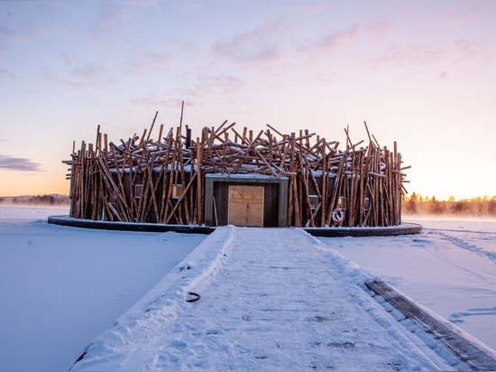 Logs splayed around the structure's facade emulate a log jam—a reference to Harads' logging industry from days of yore. During the summer, the bath floats freely in the Lule River and it's anchored...