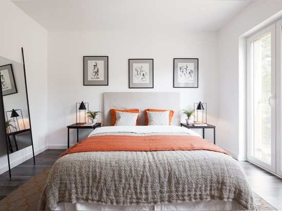 A master bedroom on the second floor gets natural light through glass doors.